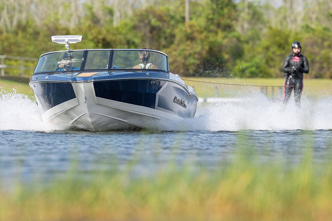 MasterCraft blue prostar with ski jumper towing behind